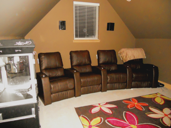 A custom media room design in a dormered bonus room
